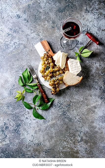 Serving board with sliced camembert cheese and baked bunch of green grapes served with bread, glass of red wine, corkscrew, green leaves