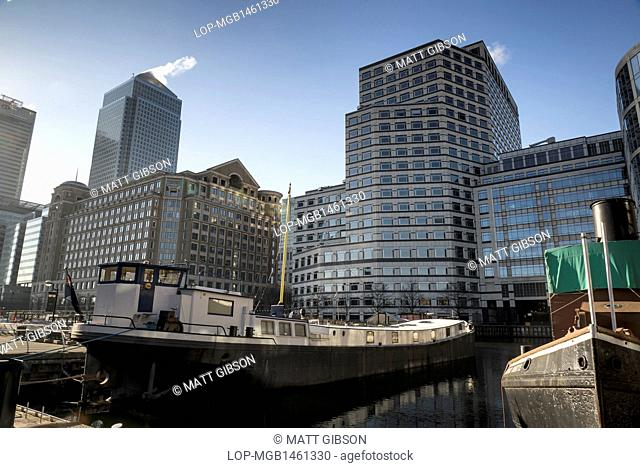 England, London, Canary Wharf. Boats in docks overshadowed by One Canada Square in the early morning
