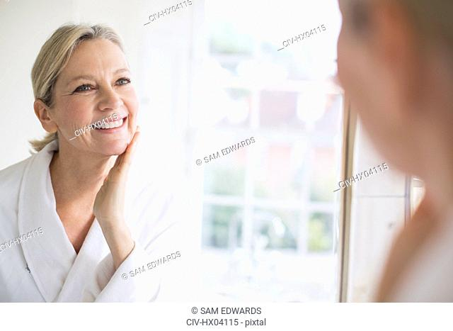 Smiling mature woman touching face at bathroom mirror