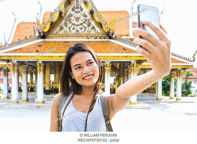 Thailand, Bangkok, portrait of smiling tourist taking selfie with smartphone
