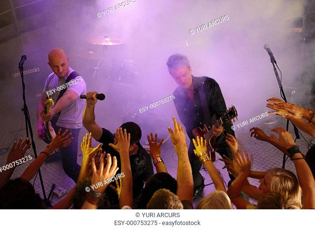 Happy people cheering at a rock band in a disco