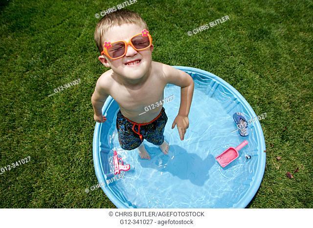 4 year old boy playing in backyard pool