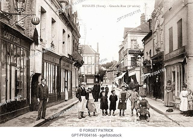 PHOTO OF THE MAIN STREET WITH ALL ITS SHOPS, OLD POSTCARD, COLLECTION OF THE CITY OF RUGLES, EURE (27), FRANCE
