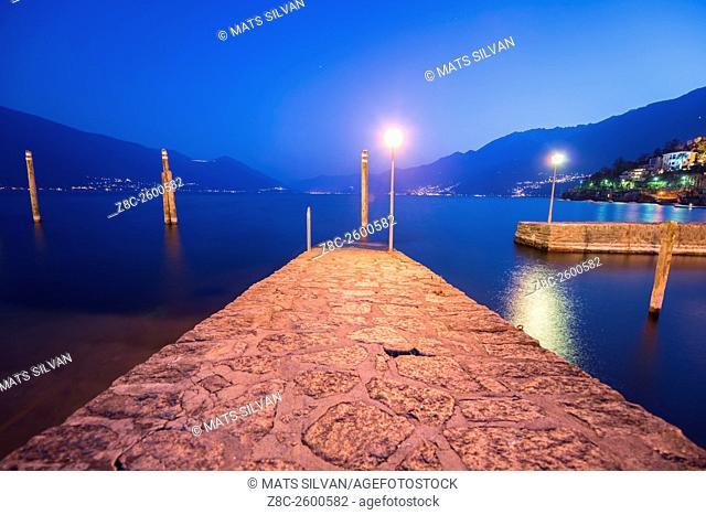 Pier on alpine Lake Maggiore in blue hour in Ascona, Switzerland