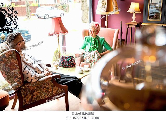 Happy quirky vintage couple having tea in tea rooms