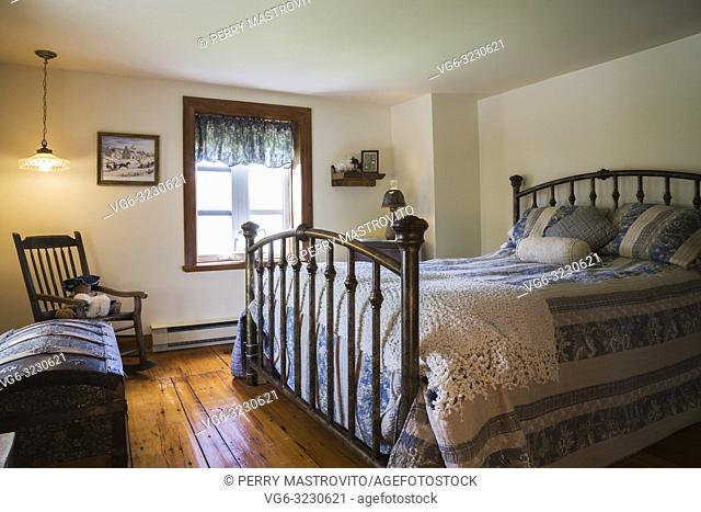 King size bed with antique wrought iron headboard and footboard, blue and white striped flowery bedspread in guest bedroom on upstairs floor inside an old 1892...