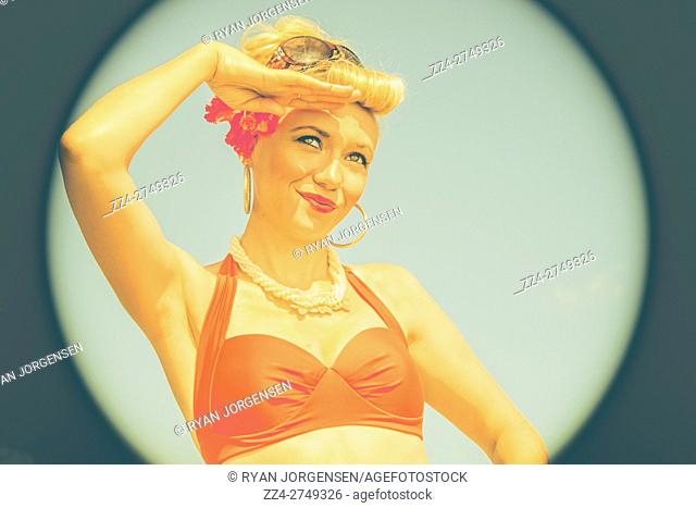 Sailoring a salute, a pop art pin-up gal in tropical attire looks out to a maritime periscope circle. Bathing beauty pinup