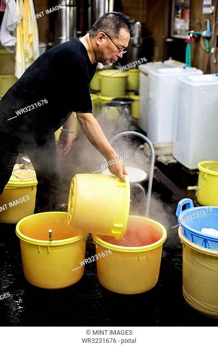 Japanese man standing in a textile plant dye workshop, pouring hot water into yellow plastic buckets