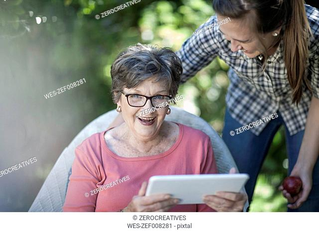 Grandmother and granddaughter in garden with digital tablet