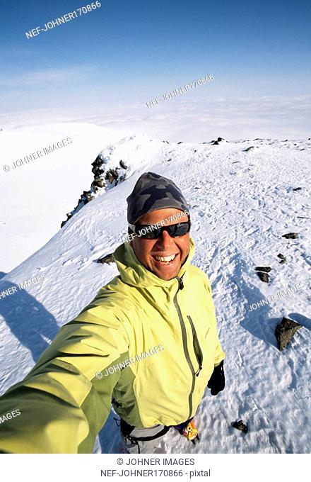 Sunburned man on top of mountain