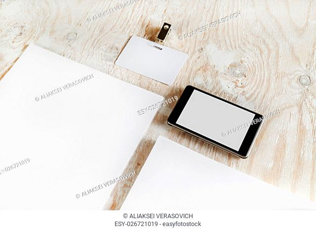 Fragment of blank stationery set. ID template on light wooden background. For design presentations and portfolios