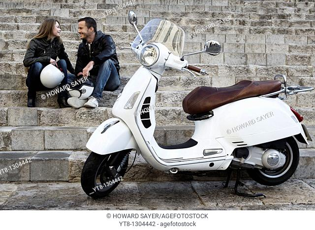 Couple sitting on steps next to motor scooter