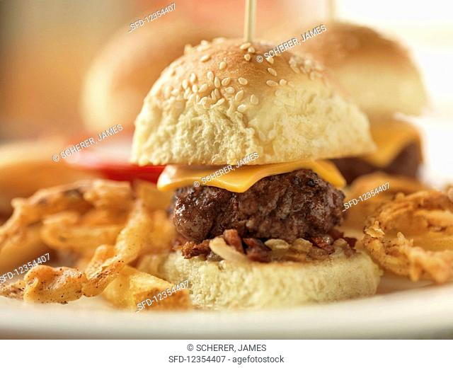 A mini cheeseburger with bacon and onions, served with fries
