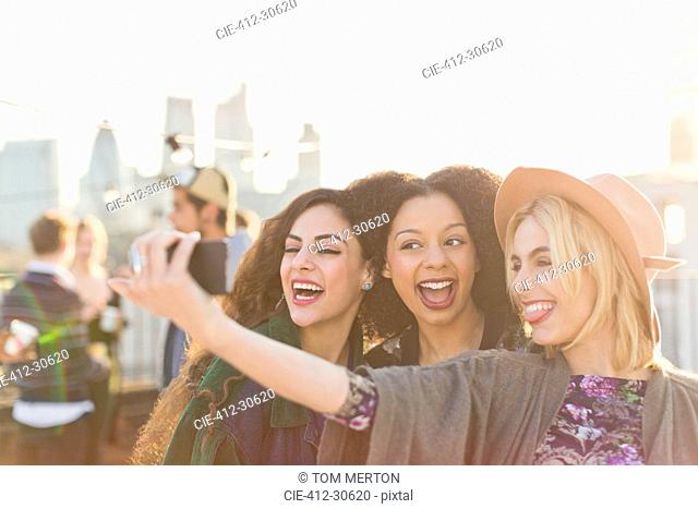 Enthusiastic young women taking selfie at rooftop party