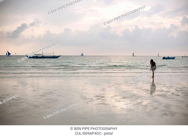 Silhouetted young woman on white beach, Boracay Island, Visayas, Philippines