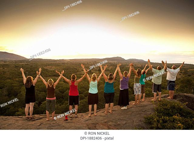 A Group Of People In A Row With Arms Raised To The Sky, Manica, Mozambique, Africa