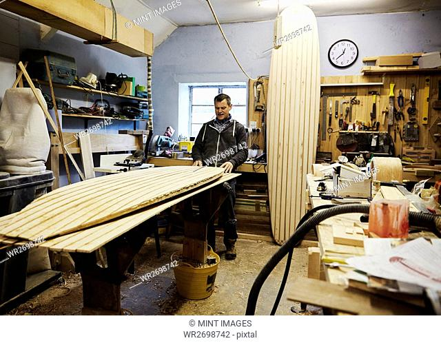 A surfboard workshop, a long board leant upright and a board in production on a workbench. Surfboard maker at work