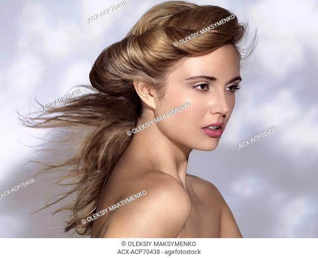 Beautiful young woman face with classic hairstyle and flying hair in a shadow of a tree against white wall background