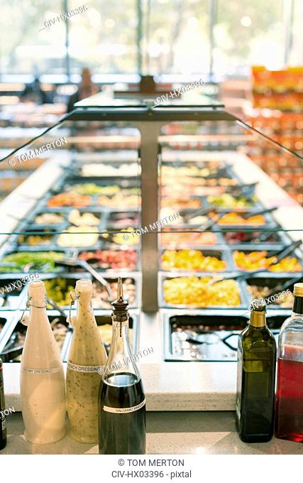 Vinegar and salad dressing on counter at salad bar in grocery store market