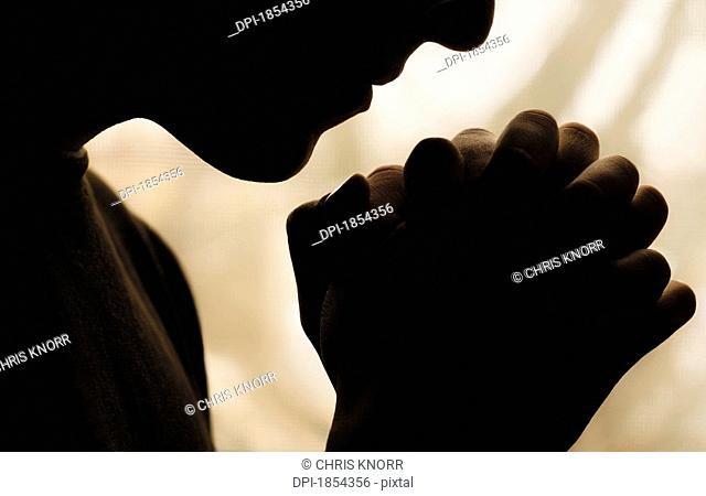 Silhouette of person praying