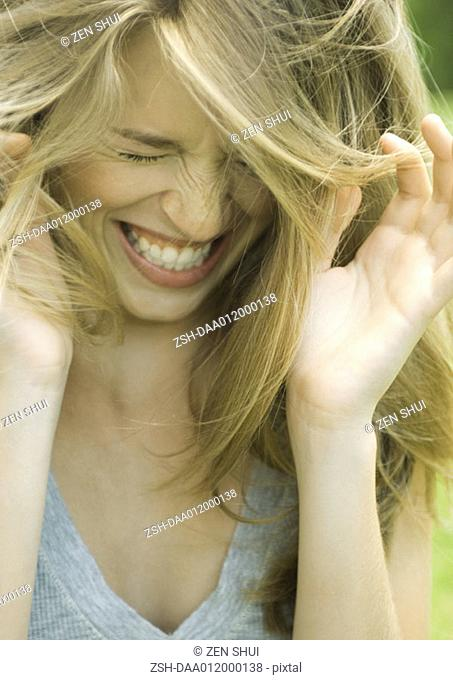 Young woman lowering head, shutting eyes and laughing with hands up
