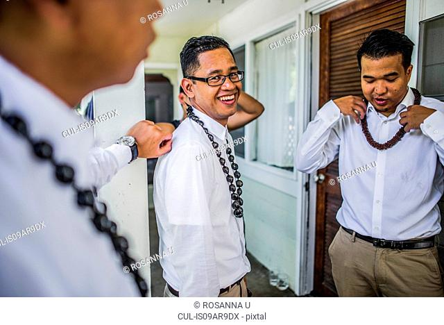 Three young men preparing for Hawaiian wedding wearing kukui nut beads, Kaaawa, Oahu, Hawaii, USA
