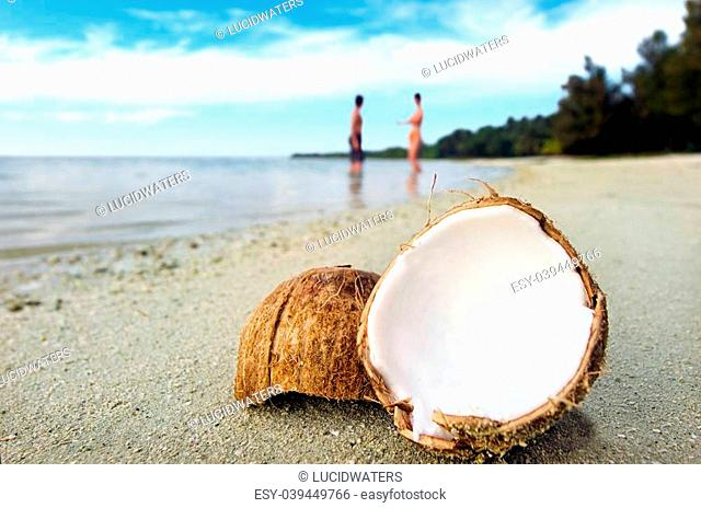 Opened coconut on sandy beach with couple bathing in the water of a deserted island in Aitutaki lagoon, Cook Island