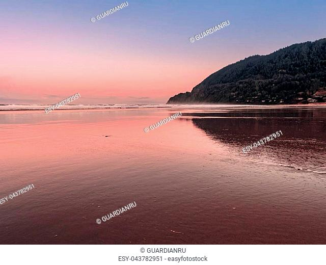 Landscape view of Neahkahnie Mountain from Manzanita Beach on the Pacific Coast of Northern Oregon. Pretty pink skies reflecting on the wet sand at sunrise