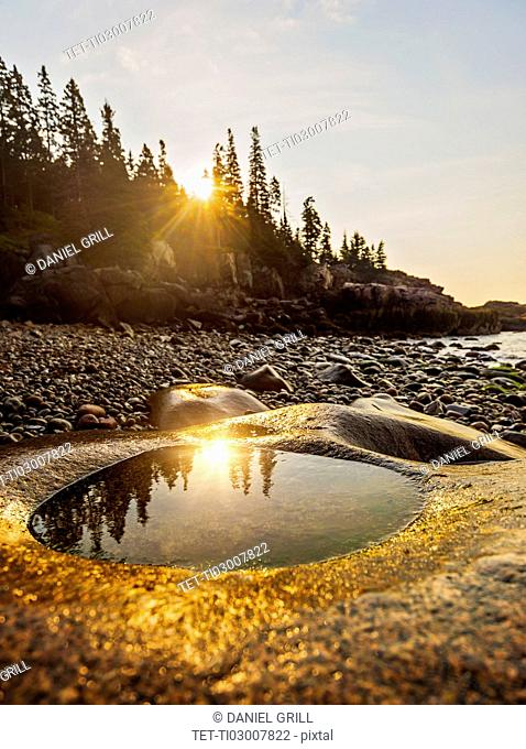 Rocks and pebbles on beach at sunrise