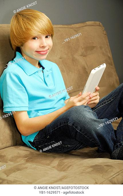 Eleven year old Caucasian boy using an e-reader or tablet computer on a couch