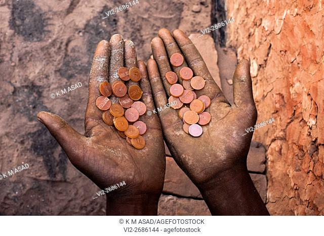 A labour shows the meager amount that he earns in coins in a brickfield covered with thick dust in Dhaka, Bangladesh, January 18, 2016