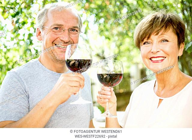 Happy senior couple having glass of red wine outdoors