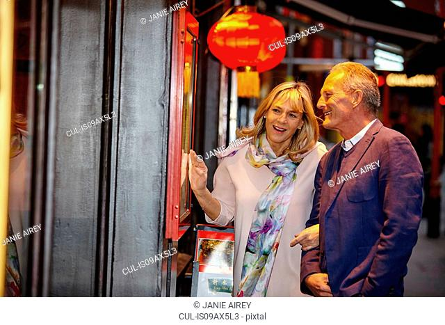 Mature dating couple reading restaurant menu in China Town, London, UK