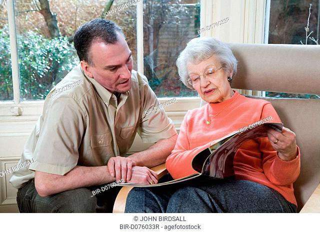 IndependentAge volunteer and older woman reading a magazine together