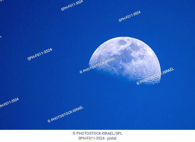Day time moon on blue sky background