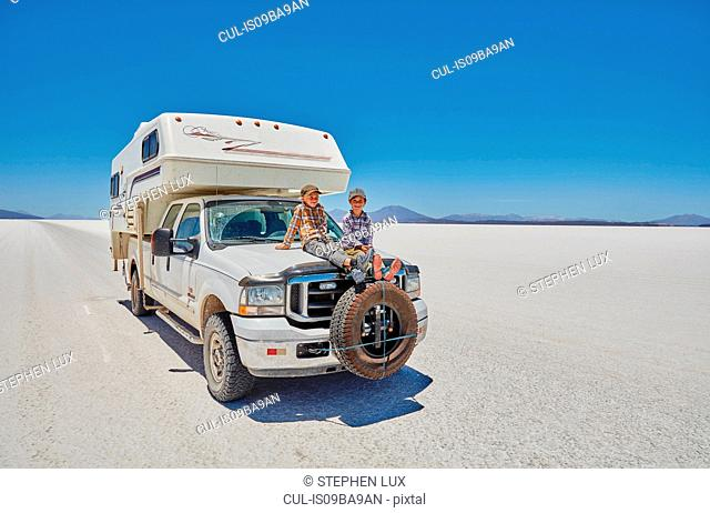 Two boys sitting on parked recreational vehicle, Salar de Uyuni, Uyuni, Oruro, Bolivia, South America