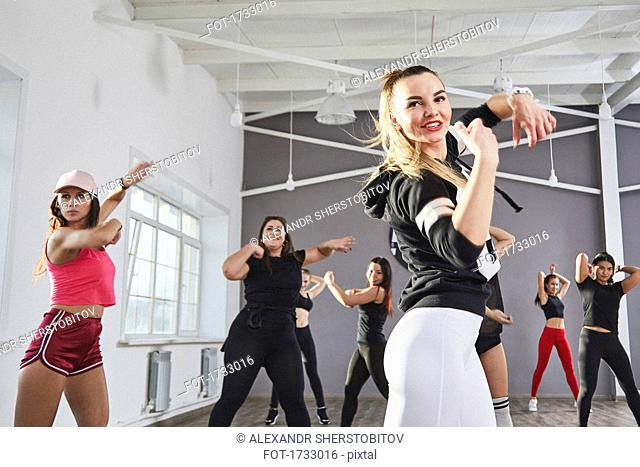 Smiling woman practicing dance with friends in studio