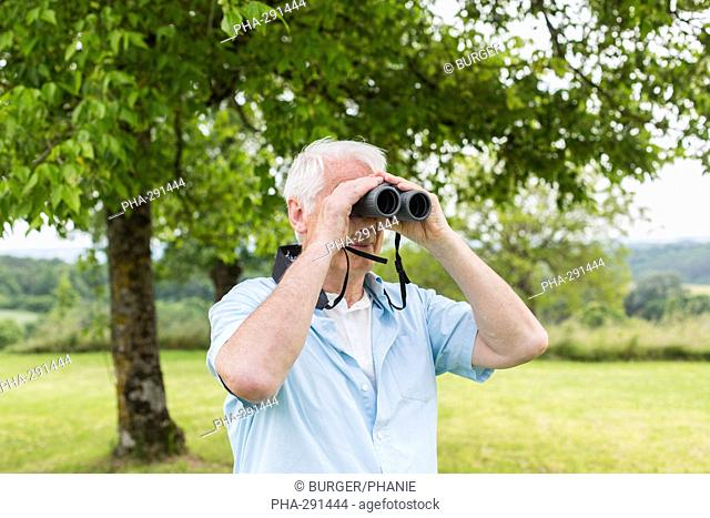 Elderly man using binoculars
