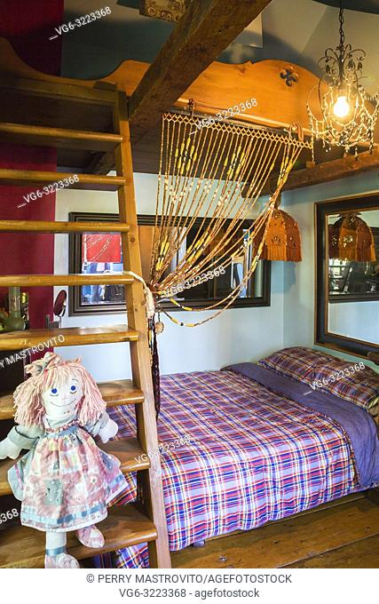 Rag doll sitting on wooden bunkbed ladder in child's bedroom on the upstairs floor inside an old circa 1850 Canadiana cottage style home