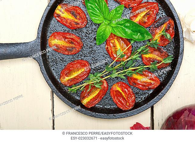 oven baked cherry tomatoes with basil and thyme on a cast iron skillet