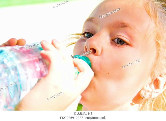 Cute girl with blond long hair drinking water
