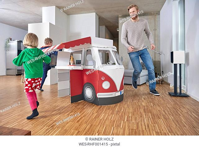 Happy father with children running around model car in living room