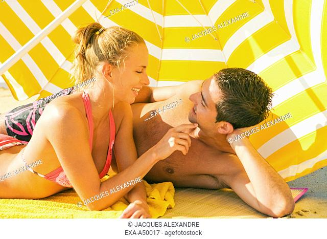 Young couple lying under a yellow umbrella on the beach smiling