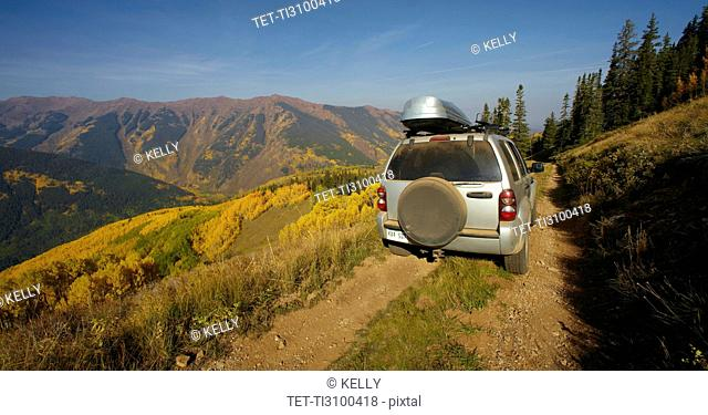 Mountain landscape with car on dirt road