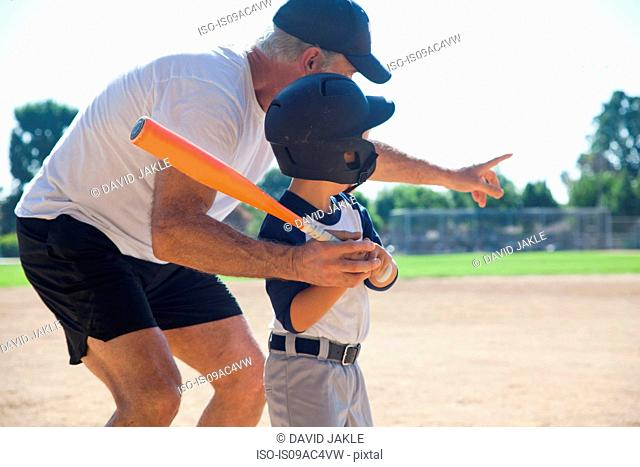 Man teaching grandson to play baseball