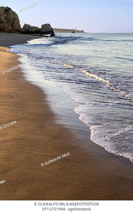 The rising sun illuminates the fine sand bathed by the blue ocean Praia do Vau Portimao Faro district Algarve Portugal Europe