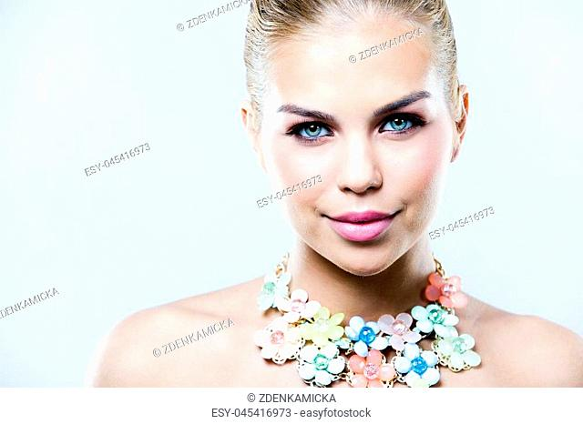 beautiful woman with dark makeup and pink lipstick posing on light background wearing flower spring and summer jewellry necklace