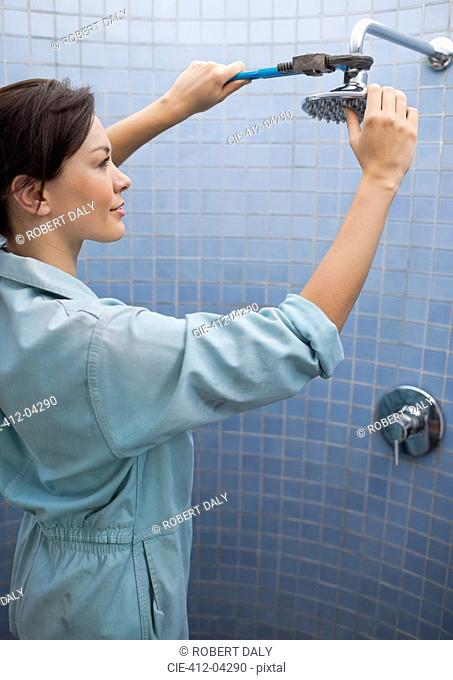 Female plumber working on shower head in bathroom