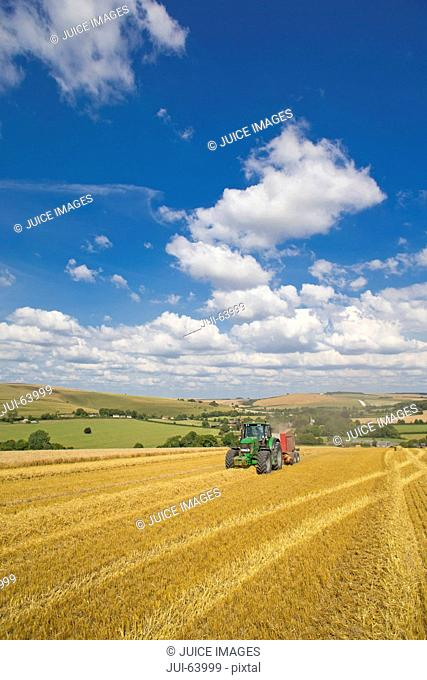 Tractor baling straw in sunny rural field