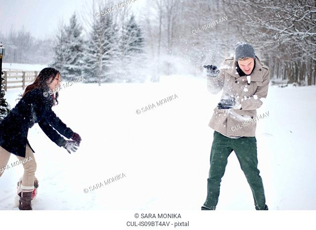 Young couple having snowball fight in snow covered forest, Ontario, Canada